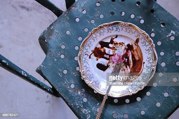 High Angle View Of Fork And Leftovers Chocolate In Plate On Table
