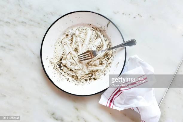 high angle view of fork and leftovers in plate with napkin on marble table - finishing stock pictures, royalty-free photos & images
