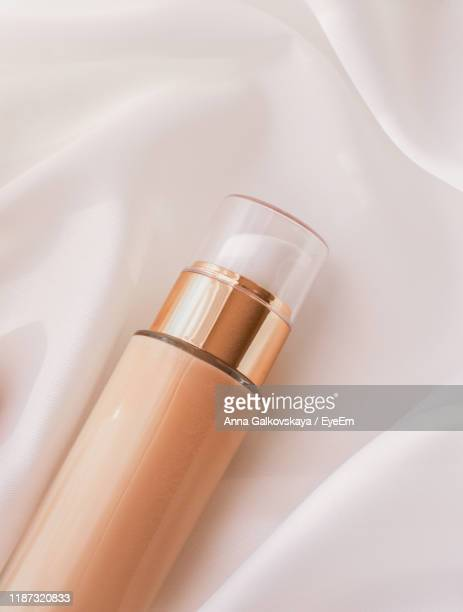 high angle view of foundation bottle against white textile - concealer stock pictures, royalty-free photos & images