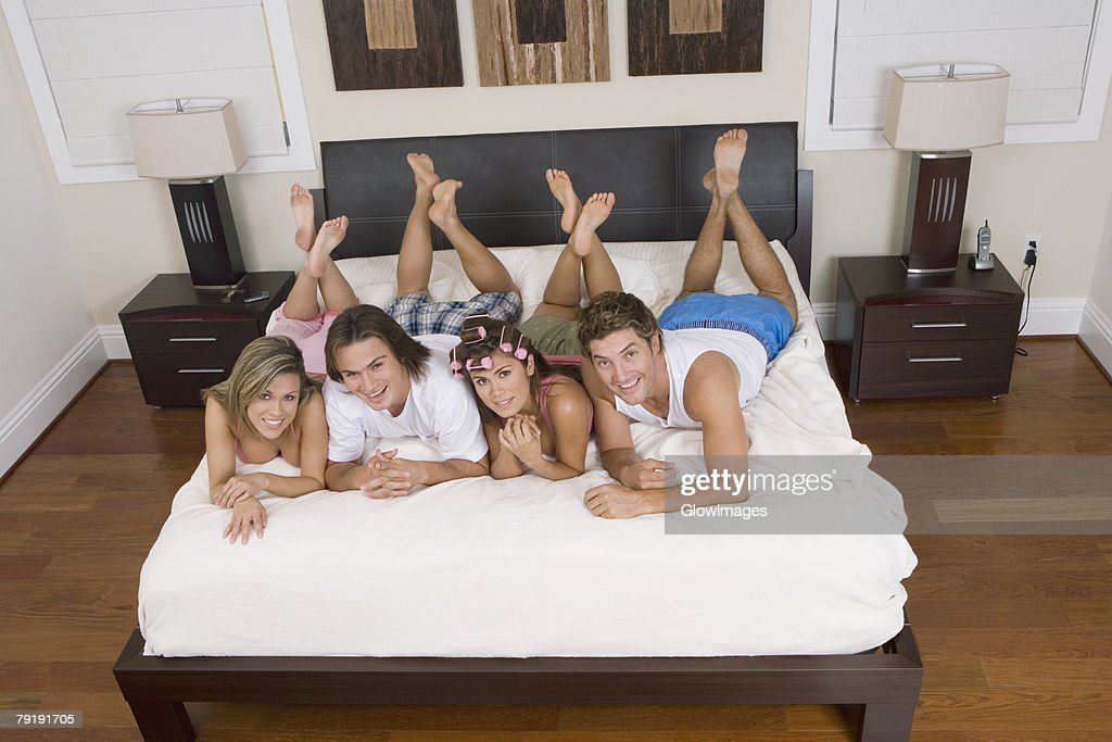 High angle view of four friends lying on the bed : Foto de stock
