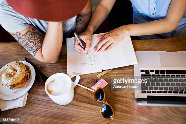 High angle view of freelancers making plan at cafe table