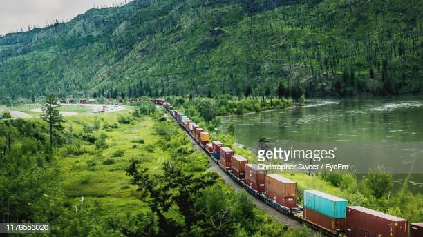 high angle view of freight train by lake against mountain - 貨物列車 ストックフォトと画像