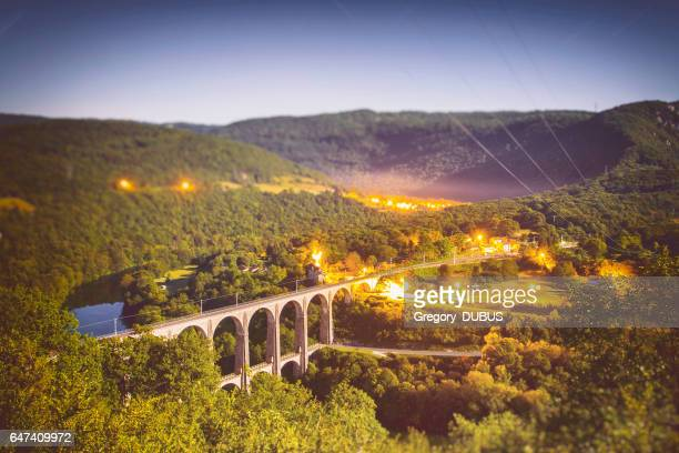 High angle view of french Bugey mountains beginning of Jura landscape by summer night with old stone railway viaduct arch bridge crossing Ain river under moonlight