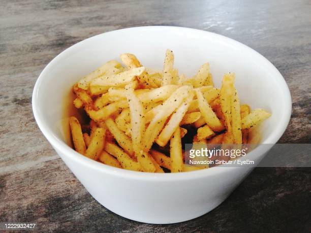 high angle view of french fries in bowl on table - fast food french fries stock pictures, royalty-free photos & images