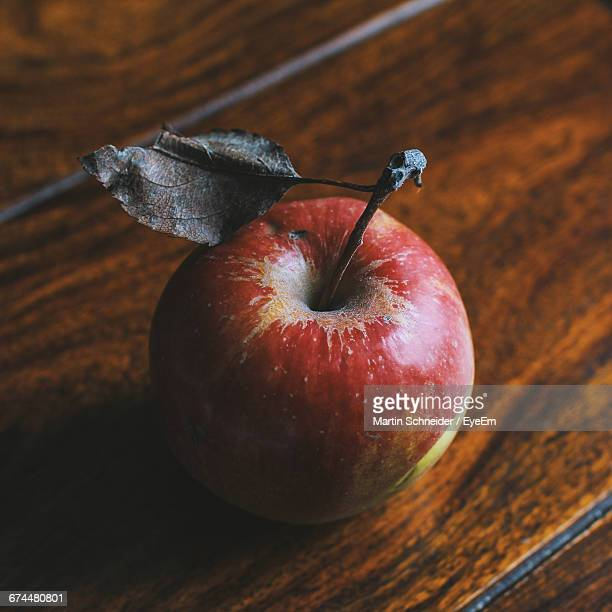 High Angle View Of Fresh Apple With Dry Leaf On Table