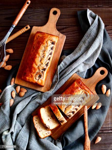 High Angle View Of Fresh Baked Bread On Cutting Boards Over Napkin With Almonds