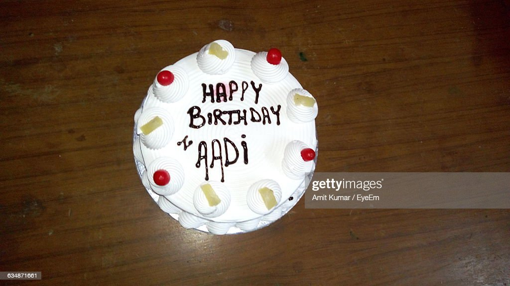 High Angle View Of Fresh Birthday Cake With Text On Table Stock