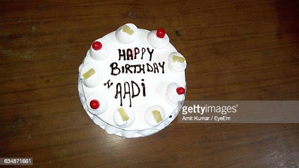 High Angle View Of Fresh Birthday Cake With Text On Table