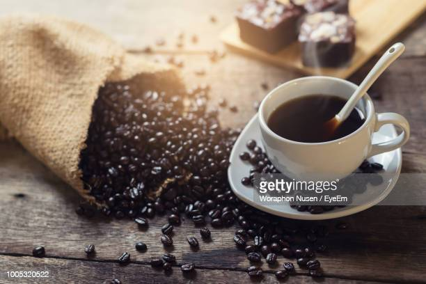 High Angle View Of Fresh Black Coffee By Roasted Beans On Table