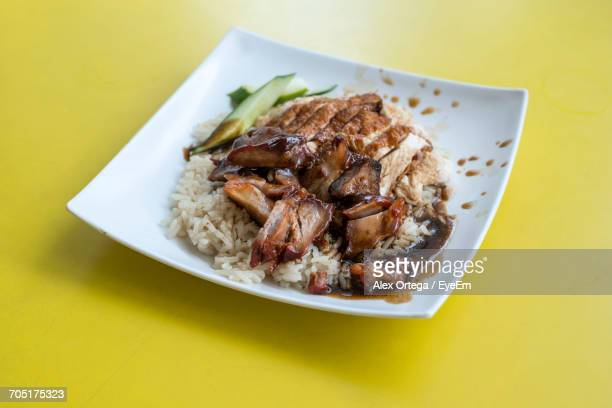High Angle View Of Fresh Char Siu Served With Chicken Meat In Plate On Yellow Background