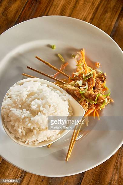 High Angle View Of Fresh Chicken Satay With Rice Served On Table