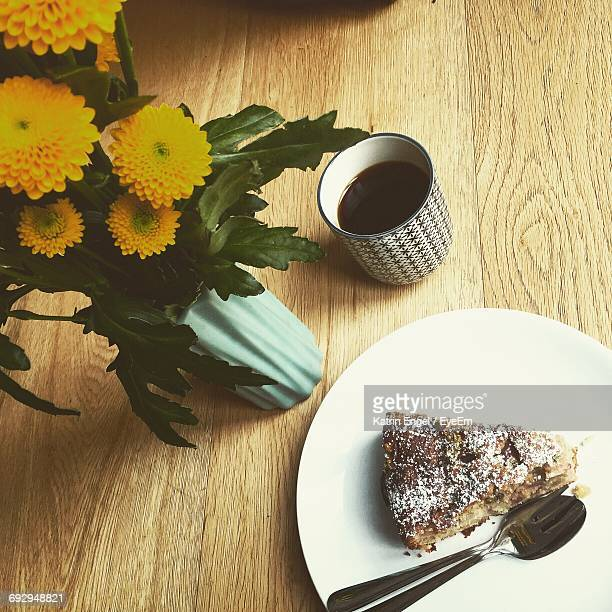 High Angle View Of Fresh Coffee And Cake By Flowers On Table At Cafe