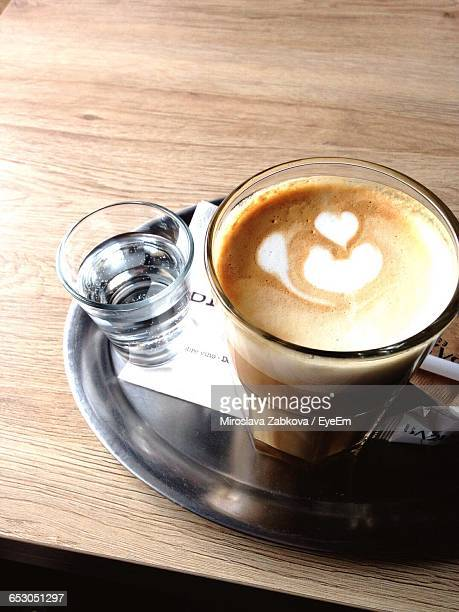 High Angle View Of Fresh Coffee And Water Served In Tray On Table At Cafe