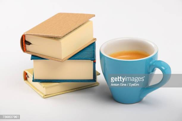 High Angle View Of Fresh Coffee By Books Stack Against White Background