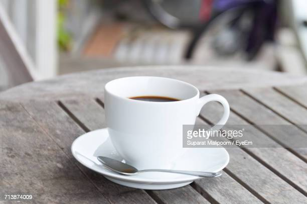 High Angle View Of Fresh Coffee Served In White Cup And Saucer On Wooden Table