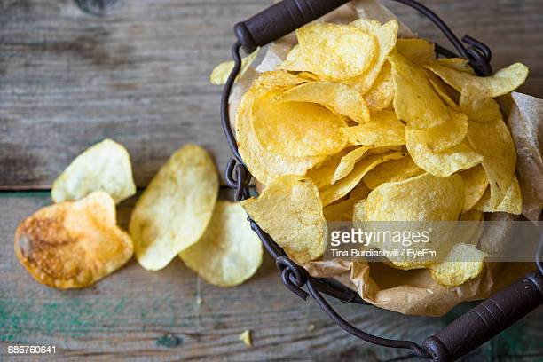 high angle view of fresh crunchy potato chips on table - ポテトチップス ストックフォトと画像