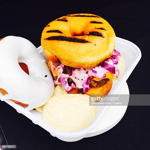 high angle view of fresh donut burger in plastic plate on table - plastic plate stock pictures, royalty-free photos & images