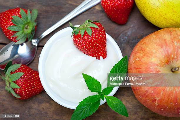 High Angle View Of Fresh Fruits And Cream Bowl On Table