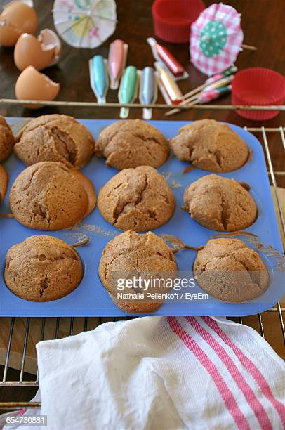 high angle view of fresh homemade cupcakes in tray on metal grate - nathalie pellenkoft stock pictures, royalty-free photos & images