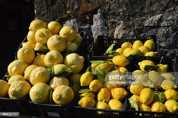 High Angle View Of Fresh Lemons In Crate Against Wall At Market Stall