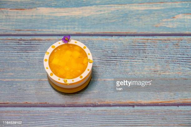 high angle view of fresh mango cake served on wooden. mango and coconut layer cakes - coulis stock pictures, royalty-free photos & images