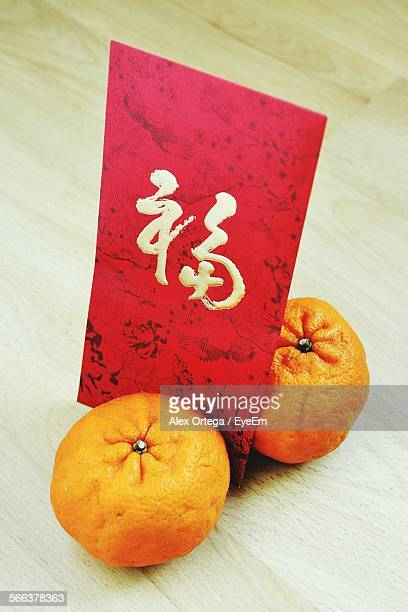 High Angle View Of Fresh Oranges By Text On Red Paper
