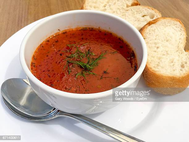 high angle view of fresh tomato soup with bread served on table - tomato soup stock photos and pictures