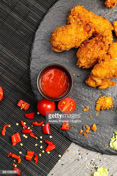High Angle View Of Fried Chicken By Sauce On Table