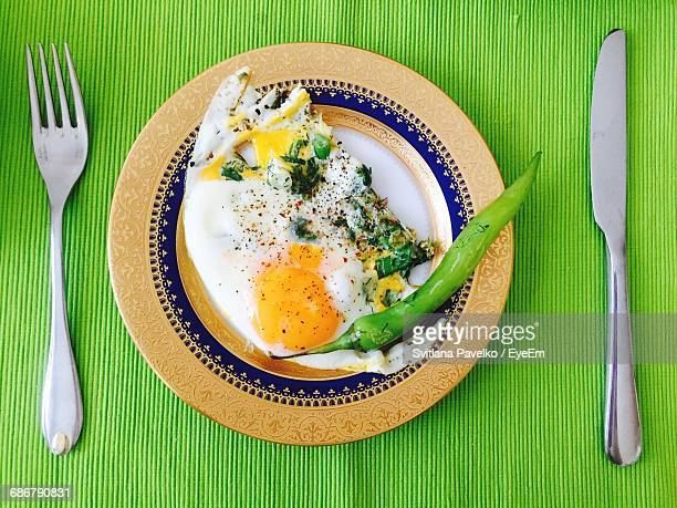 High Angle View Of Fried Egg With Green Chili Pepper In Plate On Table