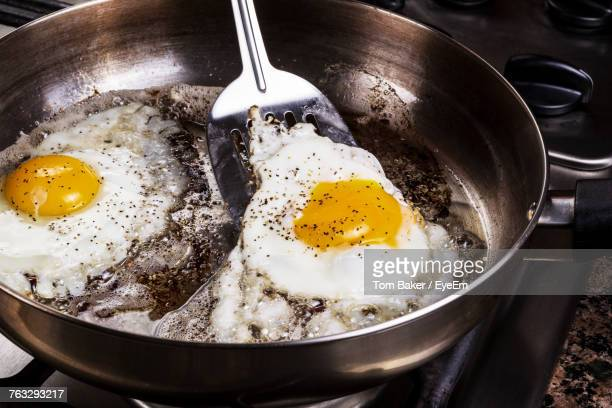 High Angle View Of Fried Eggs In Cooking Pan On Stove