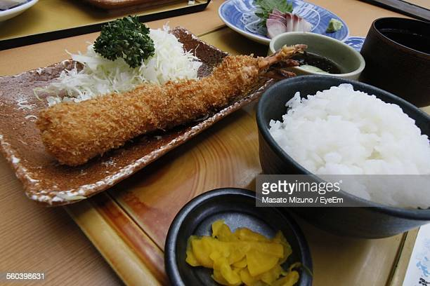 High Angle View Of Fried Prawn Served With Rice And Grated Cabbage On Table