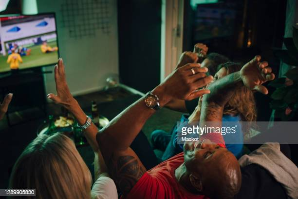 high angle view of friends cheering while watching sports on tv in living room - supporter stock pictures, royalty-free photos & images