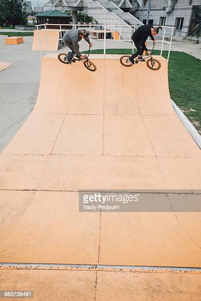 High angle view of friends cycling on ramp at skateboard park