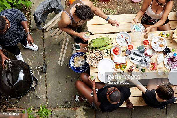 high angle view of friends eating at backyard barbecue - grelhado cozido - fotografias e filmes do acervo