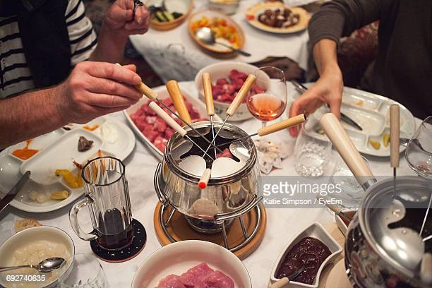 High Angle View Of Friends Eating Fondue