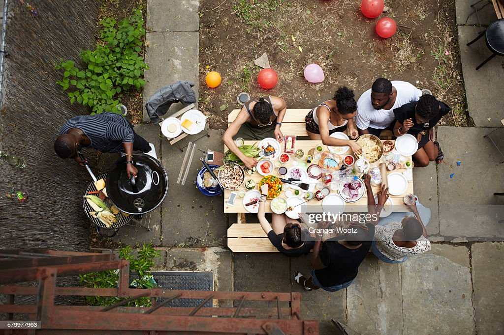High angle view of friends enjoying backyard barbecue : Foto stock