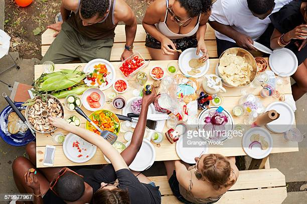 high angle view of friends enjoying backyard barbecue - picnic table stock pictures, royalty-free photos & images