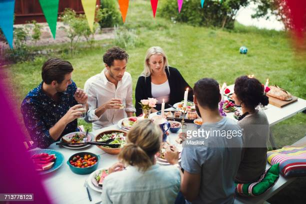 High angle view of friends enjoying dinner at garden party