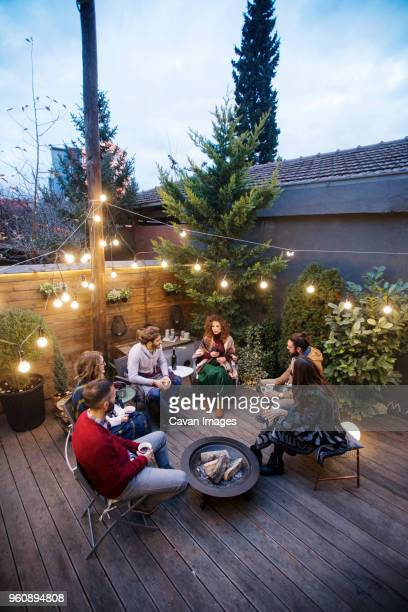 high angle view of friends enjoying drinks while sitting in backyard at dusk - fire pit stock pictures, royalty-free photos & images