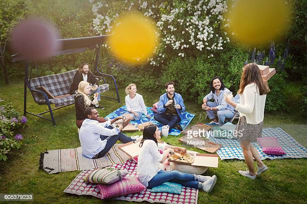 High angle view of friends having snacks during summer party at yard