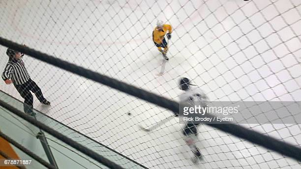 High Angle View Of Friends Playing Ice Hockey