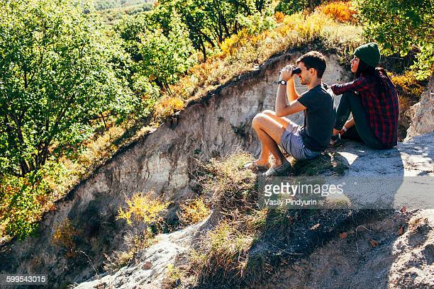 High angle view of friends sitting on mountain at forest