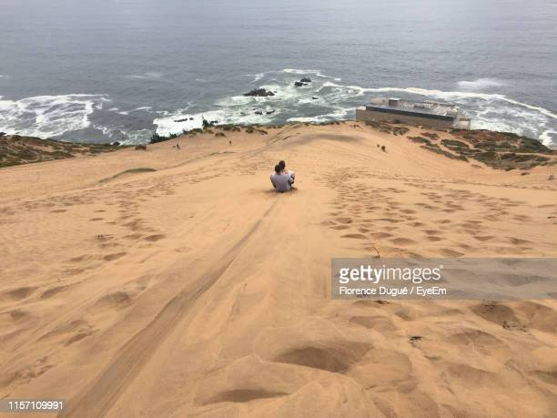 high angle view of friends sitting on sand at beach - vina del mar stock pictures, royalty-free photos & images