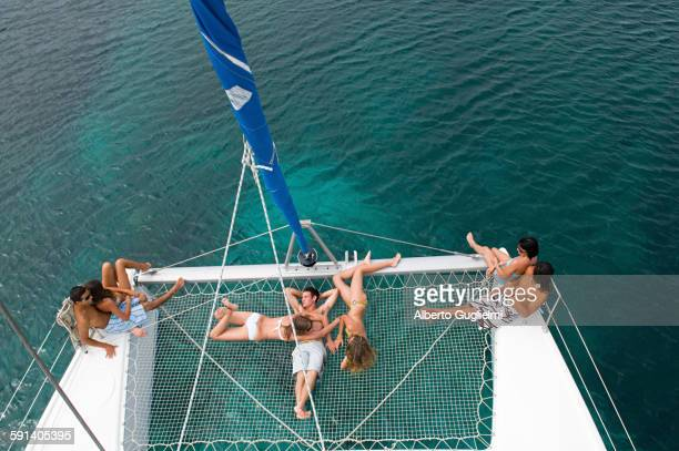 high angle view of friends sunbathing on sailboat - catamaran stock photos and pictures
