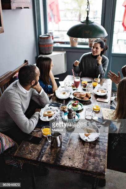 High angle view of friends talking while having food at dining table