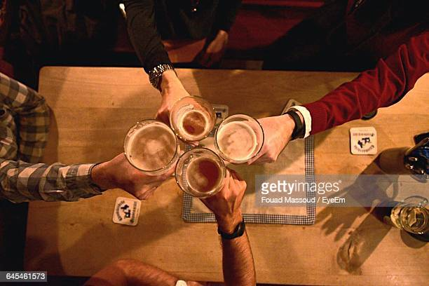 High Angle View Of Friends Toasting Beer Glasses During Party