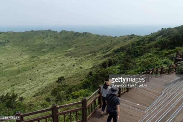 high angle view of friends walking on steps at seongsan ilchulbong against sky - jeju stock photos and pictures