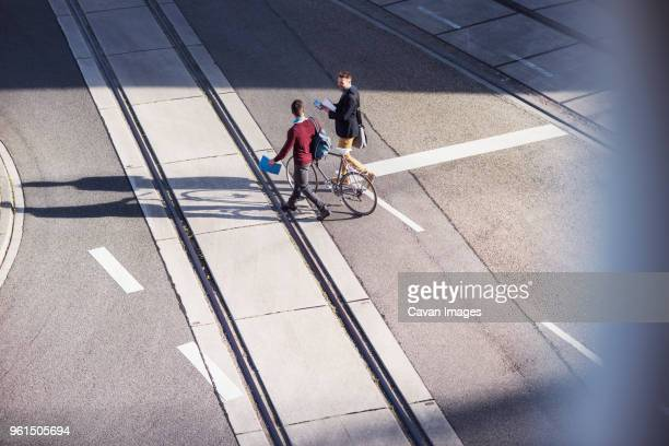 High angle view of friends walking with bicycle on road