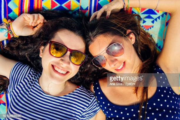 High Angle View Of Friends Wearing Sunglasses While Lying On Blanket At Beach