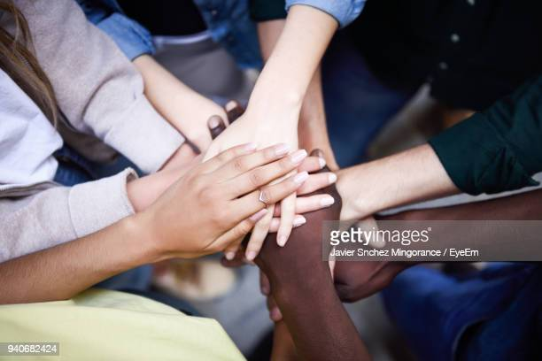 high angle view of friends with stacked hands - volunteer stock pictures, royalty-free photos & images